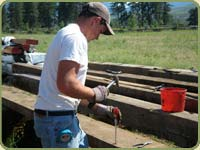 image of a bear creek lumber employee taking nails out of reclaimed lumber